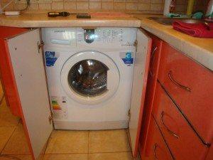אנו מתקינים את מכונת הכביסה המובנית מתחת לדלפק השיש