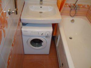 מכונת כביסה מתחת לכיור בחדר האמבטיה